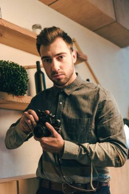 portrait of thoughtful man with photo camera standing in cafe