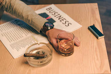 cropped shot of businessman sitting at table with glass of cognac, newspaper and cigar in ashtray in cafe
