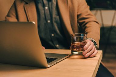 cropped shot of man with glass of whiskey sitting at table with laptop