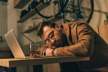 tired man sleeping on table with glass of whiskey and laptop in cafe