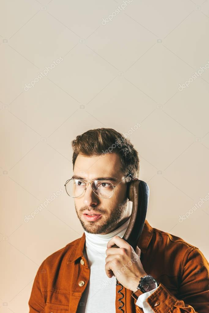 portrait of pensive stylish man looking away while talking on telephone isolated on beige