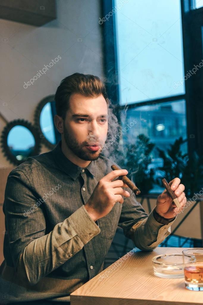 portrait of handsome man smoking cigar in cafe