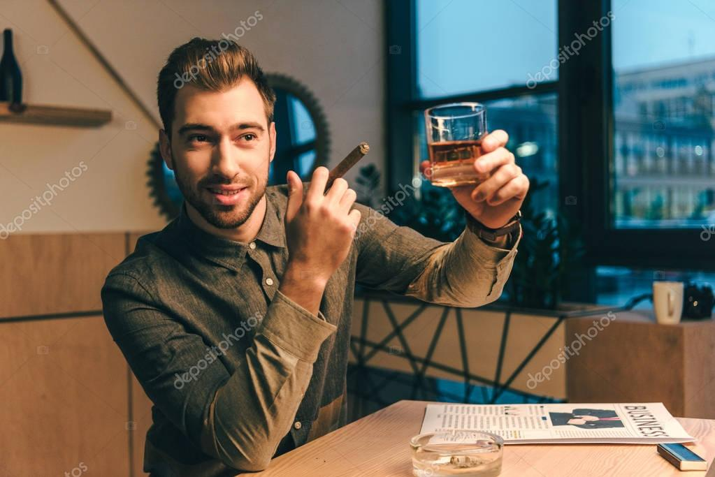portrait of businessman with cigar holding glass of cognac in cafe