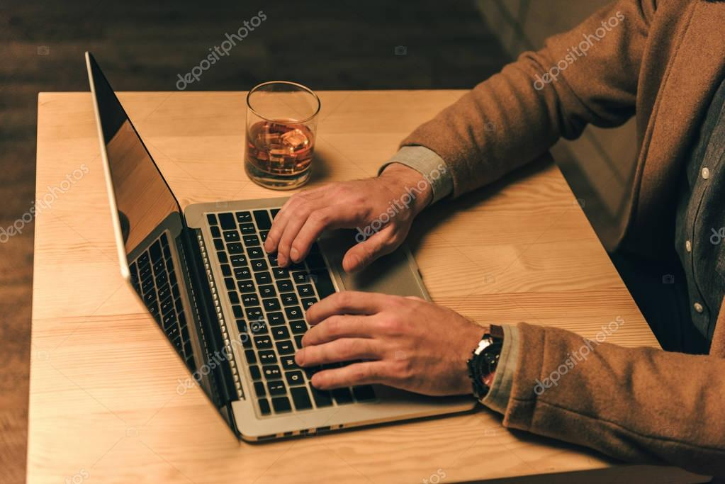 cropped shot of man typing on laptop at table with glass of whiskey