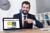 portrait of smiling businessman pointing at laptop at workplace in office