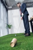 selective focus of young businessman playing golf in office
