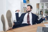 smiling businessman with golf equipment at workplace in office