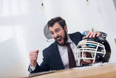 excited businessman with rugby helmet at workplace in office