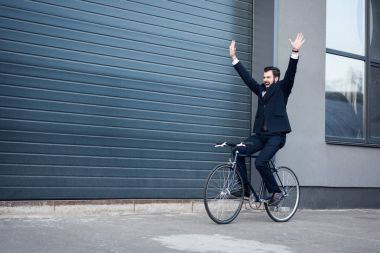 excited young businessman with outstretched arms riding bicycle on street