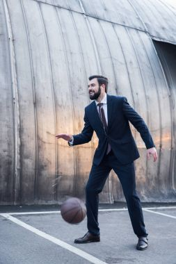 side view of cheerful businessman in earphones playing basketball on street