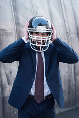 portrait of excited businessman in suit and rugby helmet on street