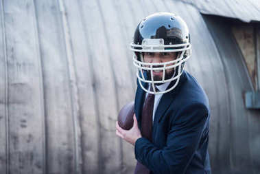 angry businessman in suit and rugby helmet with ball in hands on street