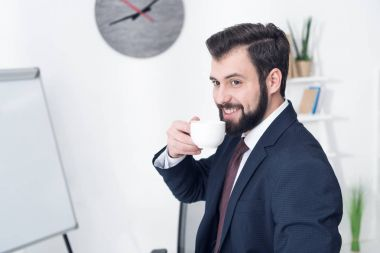 Portrait of smiling businessman drinking coffee in office stock vector