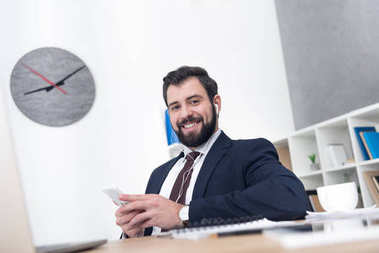 businessman listening music in earphones with smartphone at workplace in office