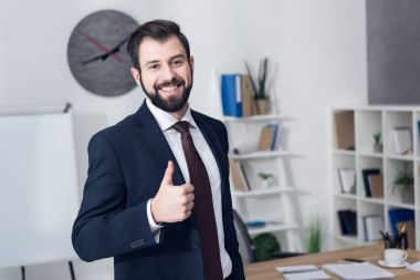 Portrait of smiling businessman showing thumb up in office stock vector