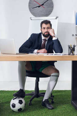 tired businessman with soccer ball sitting at workplace in office