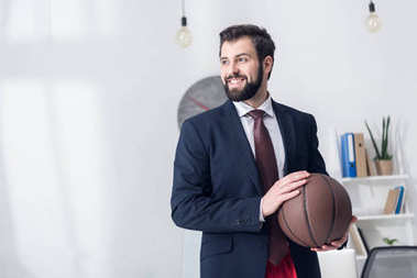 portrait of businessman in jacket holding basketball ball in office