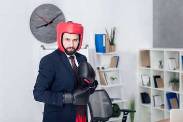 portrait of young businessman in boxing equipment in office
