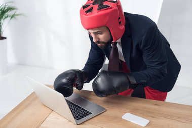 businessman in boxing gloves and helmet typing on laptop at workplace in office