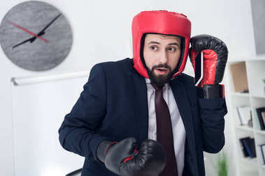 portrait of businessman in boxing gloves and helmet  talking on smartphone in office