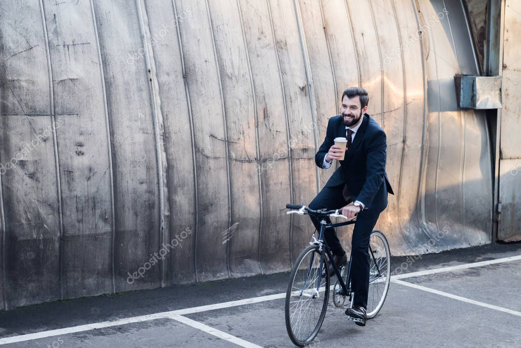 smiling businessman in suit with coffee to go in hand riding bicycle