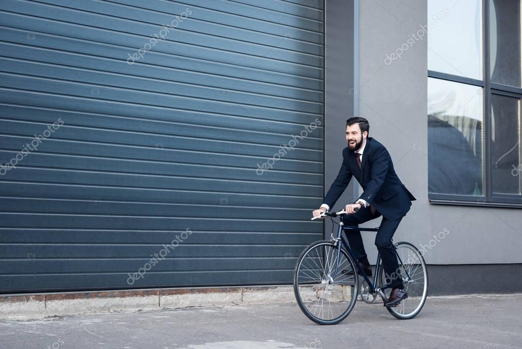 smiling young businessman in suit riding bicycle on street
