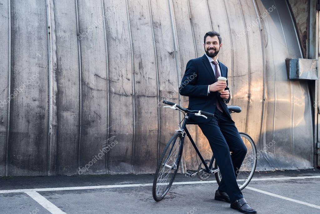smiling businessman with disposable cup of coffee leaning on bicycle on street