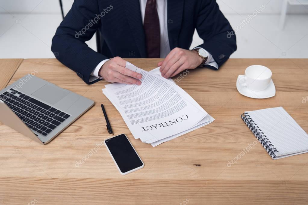 partial view of businessman with contract sitting at workplace in office