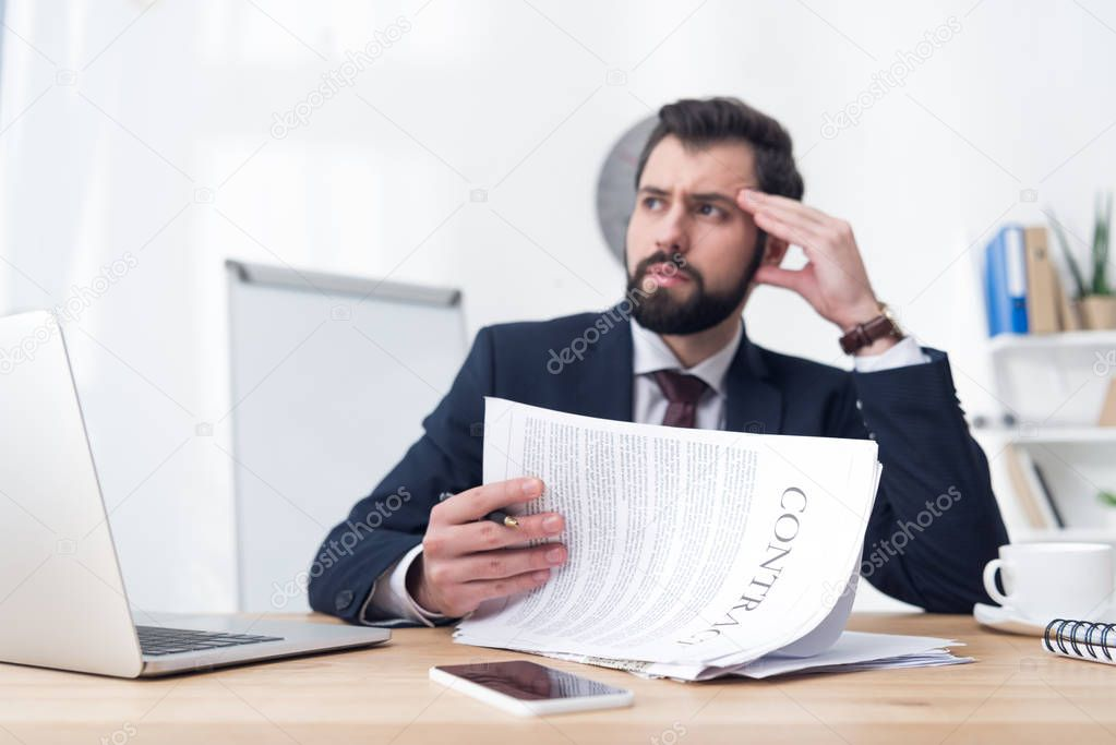 pensive businessman with contract sitting at workplace in office