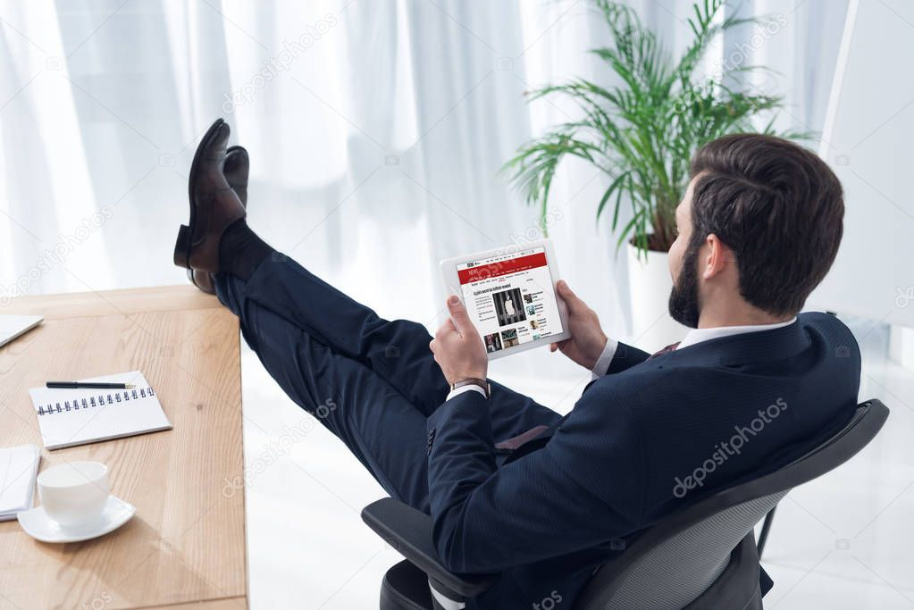 side view of businessman using tablet at workplace in office