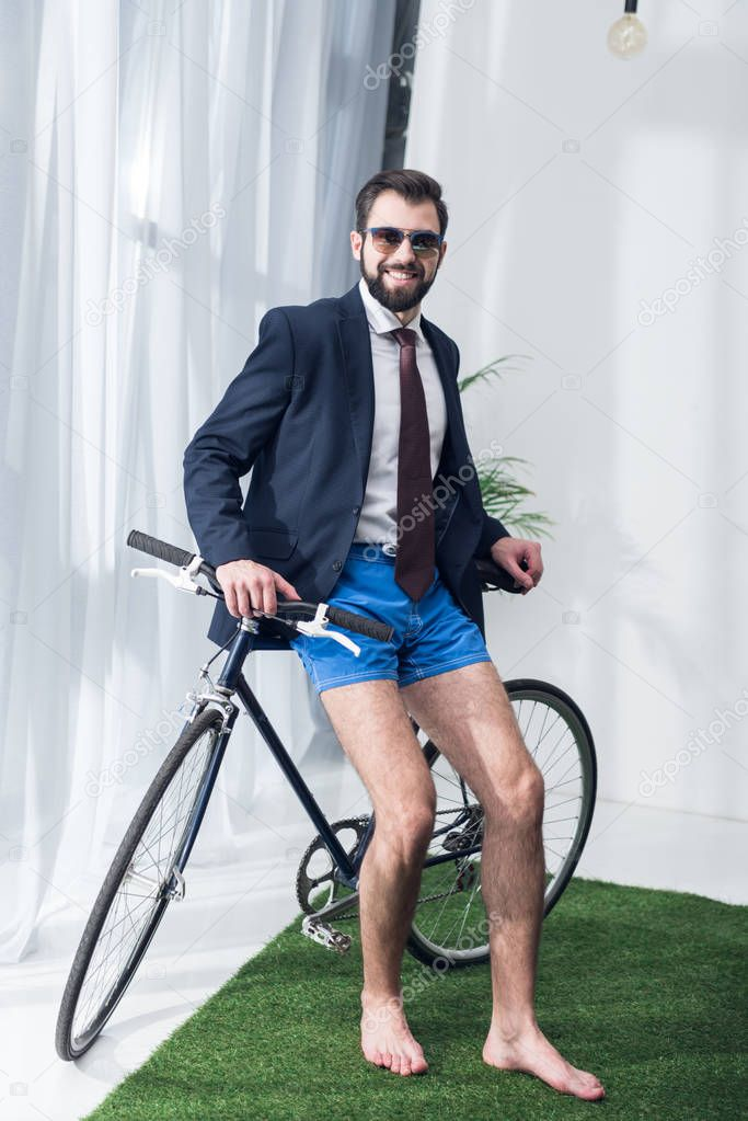 smiling businessman in jacket and shorts leaning on bicycle in office