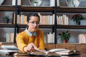 young student girl preparing for exam at library and reading book