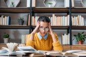 Fotografia ragazza dellallievo stanco preparazione per esame presso la biblioteca e che tiene la testa con le mani