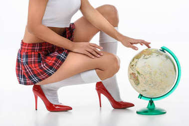cropped shot of sexy schoolgirl in red plaid skirt with globe on white