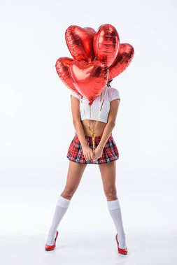 sexy schoolgirl covering face with helium balloons in shape of hearts isolated on white