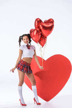 Young sexy schoolgirl with helium balloons in shape of hearts in front of big red heart on white stock vector