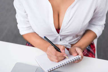 cropped shot of woman in unbuttoned shirt writing in notebook