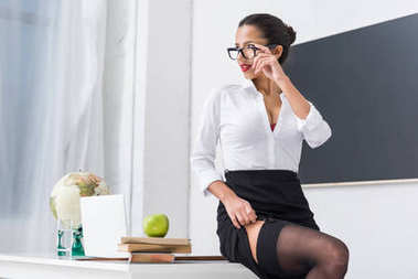 young sexy teacher in stockings sitting on desk at classroom