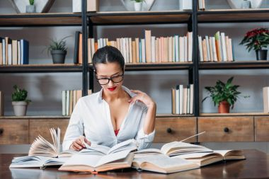 young sexy teacher in unbuttoned shirt reading at library