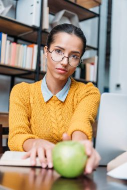 young student girl preparing for exam at library and holding green apple