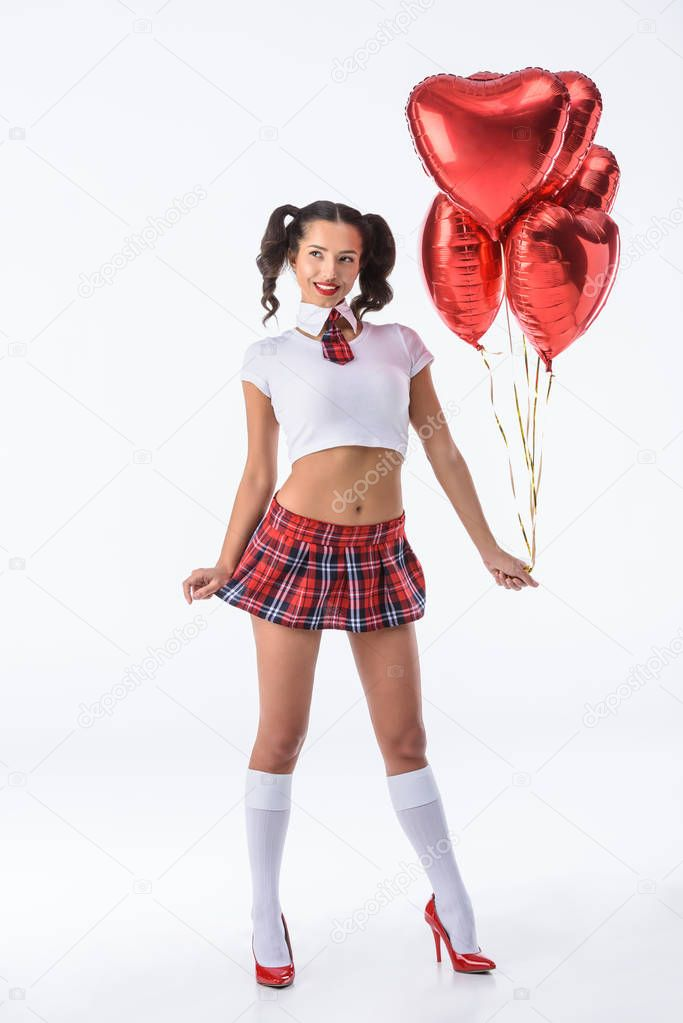 young sexy schoolgirl with helium balloons in shape of hearts isolated on white