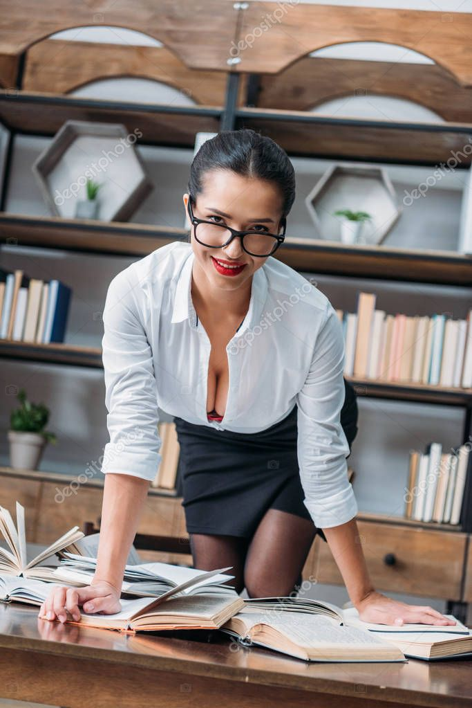 young sexy teacher in unbuttoned shirt on table at library