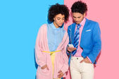 beautiful couple listening to music on smartphone on pink and blue background