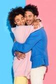 szép fiatal pár átölelte egymást a rózsaszín és a kék háttér