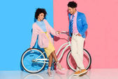 attractive couple having fun with bicycle on pink and blue background