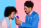 handsome man presenting flowers to attractive african woman on pink and blue background