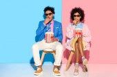 Fotografie junge afrikanische amerikanische paar sitzen auf Stühlen und Essen Popcorn gegen rosa und blauen Wand