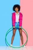 Frau in Sportbekleidung steht mit Reifen auf rosa und blauem Hintergrund