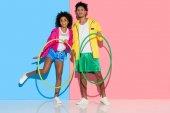 Sportliches Paar, das mit Reifen vor rosa und blauen Hintergrund in die Kamera blickt