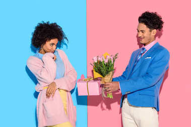 handsome man presenting box and flowers to woman on pink and blue background